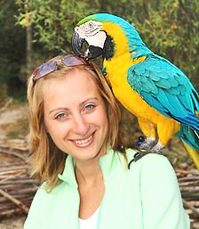 big parrot standing on a women shoulder