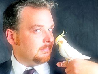 men holds a parrot on his finger